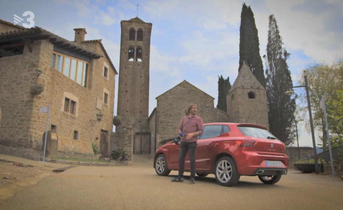 Un cotxe i el conductor davant de l'església Sant Pere de Llorà